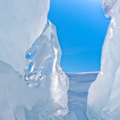 Narrow icy glacier crevasse with snow and blue sky — Stock Photo