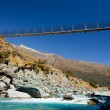 Swing bridge high over glacial river New Zealand — Stock Photo