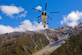 Rescue helicopter fly over mountainous wilderness — Stock Photo