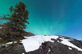 Northern Lights Aurora borealis over snowy rocks — Stock Photo