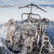 Stock Photo: Bizarre burnt out snowmobile on Yukon lake Canada