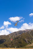 Transport helicopter fly over mountain wilderness — Stock Photo