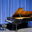 Open grand piano on stage with blue velvet cutain — Stock Photo