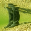 Rubber boots or gumboots underwater on sand ground — Stock Photo