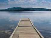 Wooden dock on a beautiful calm Yukon lake Canada — Stock Photo