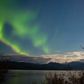 Aurora borealis moon-lit clouds over Lake Laberge — Stock Photo