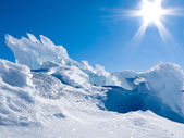 Glacier ice chunks with snow and sunny blue sky — Stockfoto