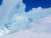 Clear glacier ice chunks with snow and blue sky — Stock Photo