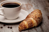 Cup of black coffee and croissant — Stock Photo