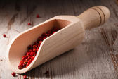 Red peppercorns in wooden scoop — Stock Photo