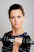Severe girl with dumbbell — Stock Photo