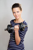 Smiling girl with dumbbell — Stock Photo