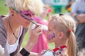 Painting at a girl's face — Stockfoto