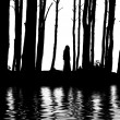 Silhouette woman between trees water reflections — Stock Photo