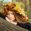 Serious girl in yellow leaves — Stock Photo