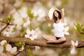 Woman sitting on tree — Stock Photo