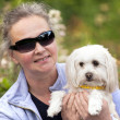 Mature woman holdiong her puppy — Stock Photo