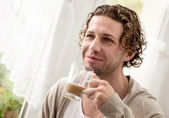 Man standing by a window drinking coffee — Stock Photo