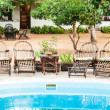 Stock Photo: Chairs on swimming pool border