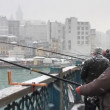 Man fishing in snowfall on Galata Bridge — Stock Video