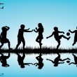Group of children silhouettes playing outdoor near a lake — Stock Photo