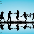 Group of children silhouettes playing outdoor near a lake — Stock Photo #37147247