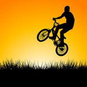 Silhouette of a biker jumping in the sunset — Stock Photo
