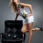 Blond girl near leather armchair — Stock Photo