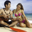 Couple on beach with ukulele - Foto Stock