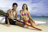 Coppia sulla spiaggia con paddleboard — Foto Stock