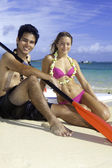 Couple on the beach with paddleboards — Stock Photo