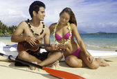 Couple on beach with ukulele — Stock Photo