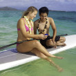 Couple texting on a paddle board — Stockfoto