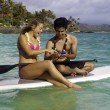 Couple with cell phone on paddle board — Stock Photo #26158593