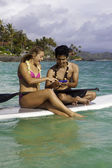 Couple with cell phone on paddle board — Stock Photo