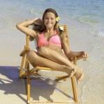 Girl in bikini on a beach chair — Stock Photo #26511407