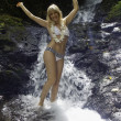 Blond woman in a waterfall — Stockfoto