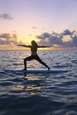 Woman doing yoga on a paddle board — Foto Stock