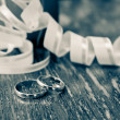 Wedding gold rings of the groom and the bride on a table — Stock Photo