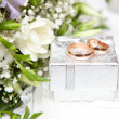 Wedding rings, gift box and flowers for the bride. - Stock Photo