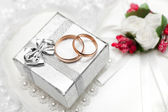 Wedding rings, gift box and flowers for the bride. — Stockfoto
