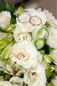 Gold wedding rings on flower — Stock Photo