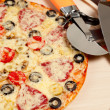 Cook pizza on a cutting board with a round knife and spatula - Stock Photo