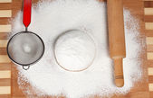 Battledore, sieve and finished dough on a cutting board. — Stock Photo