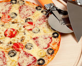 Cook pizza on a cutting board with a round knife and spatula — Stock Photo