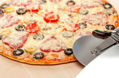 Cook pizza on a cutting board with a round knife and spatula. isolated — Stock Photo