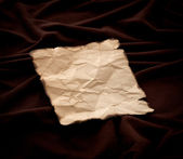 Leaf of old crushed paper against dark fabric — Stock Photo