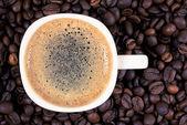 En kopp kaffe är på bakgrund av rostade kaffebönor — Stockfoto