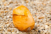 Amber on sand — Stock Photo