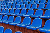 Blue plastic chairs on a football tribune — Stock Photo